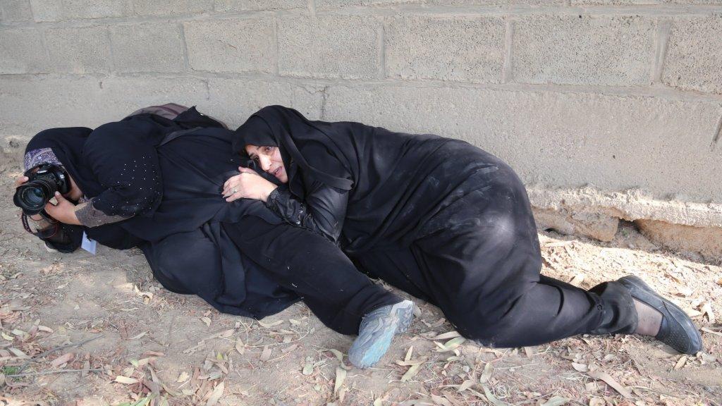 Iraanse vrouwen duiken weg tijdens de aanslag.