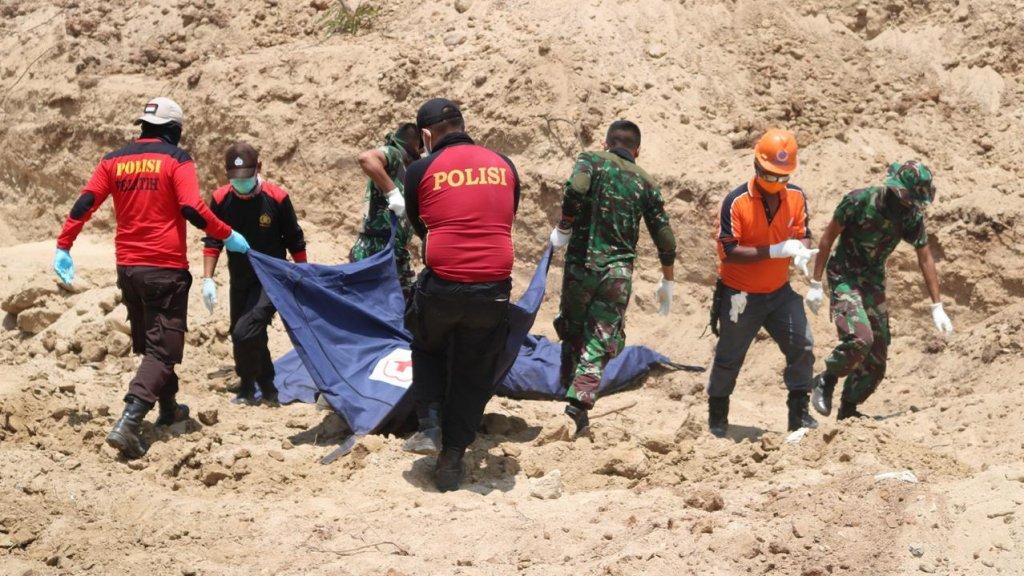Hulpverleners dragen slachtoffers naar het massagraf