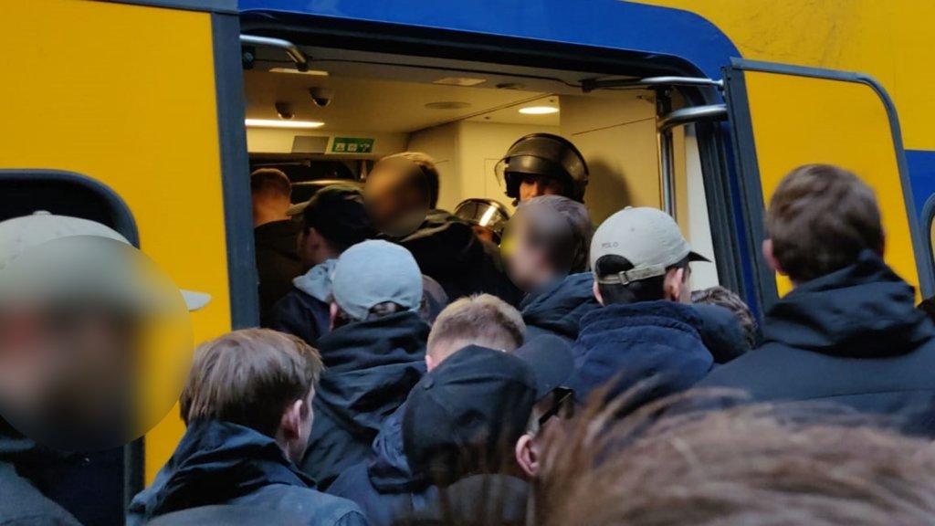 De fans worden in de trein naar het stadion gezet.