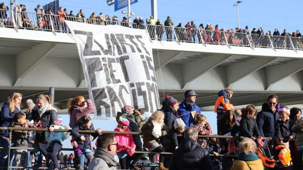 Anti-pietdemonstranten hebben een spandoek aan de Erasmusbrug in Rotterdam gehangen