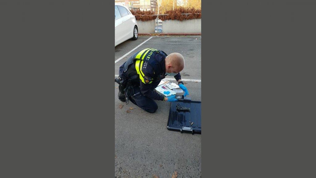 Een agent bestudeert het pistool.