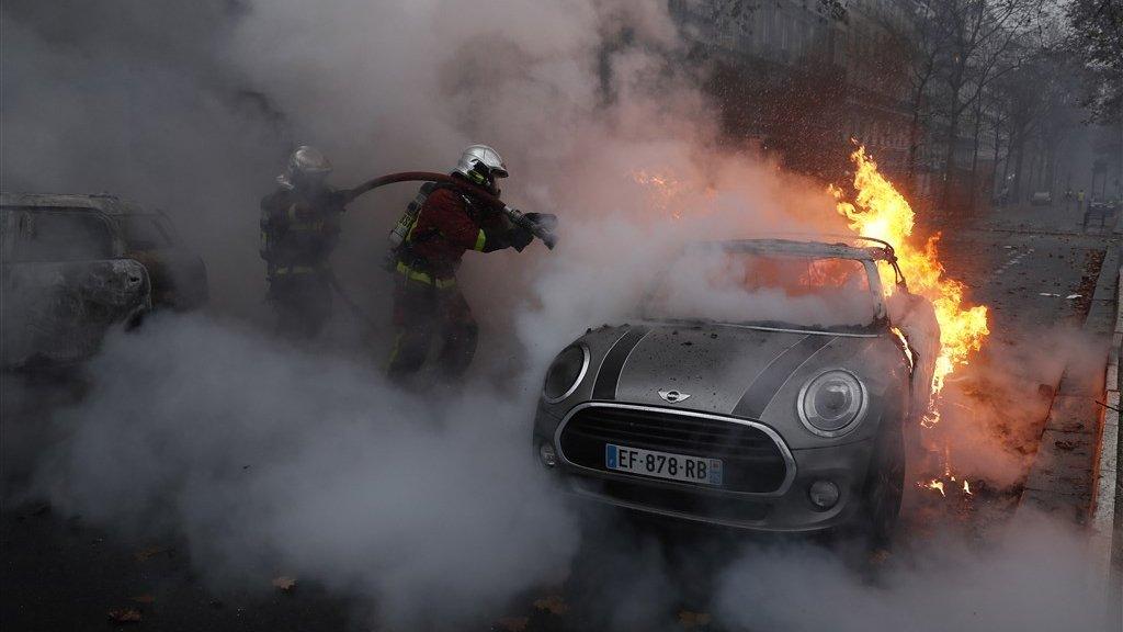 Brandweermannen blussen een in de brand gestoken auto.