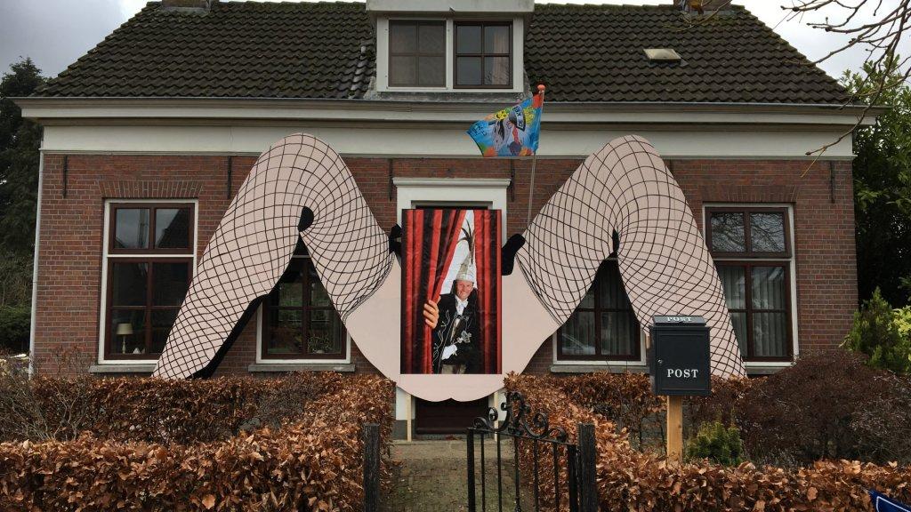 Gespreide vrouwenbenen op gevel huis brabantse prins carnaval