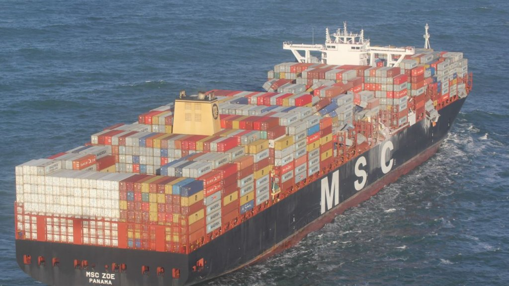 Het schip op zee. Aan de rechterzijde zijn omgeslagen containers te zien.