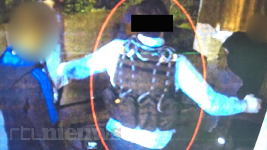 Een van de verdachten draagt een bomvest en spreidt zijn armen.