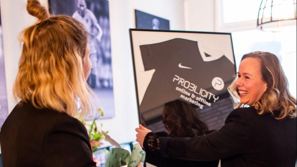 Leoni Blokhuis (R) en haar collega Eefje Janus ontvingen een ingelijst voetbalshirt tijdens de opening van het nieuwe kantoor