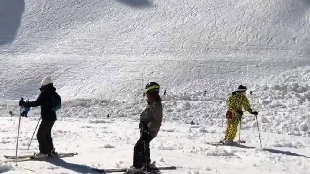 Skiërs kijken naar de plek van de lawine.