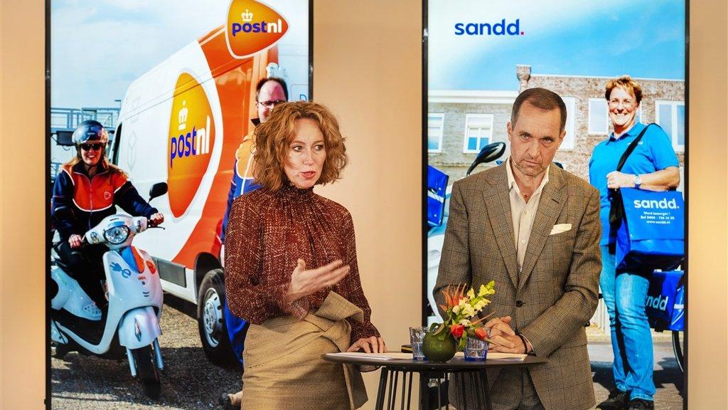 Herna Verhagen van PostNL en Ronald van de Laar van Sandd bij de presentatie van de overname.