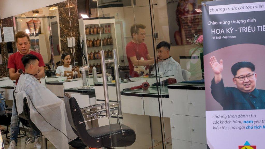Een lokale Vietnamese kapper meet een klant een 'Kim-kapsel' aan.