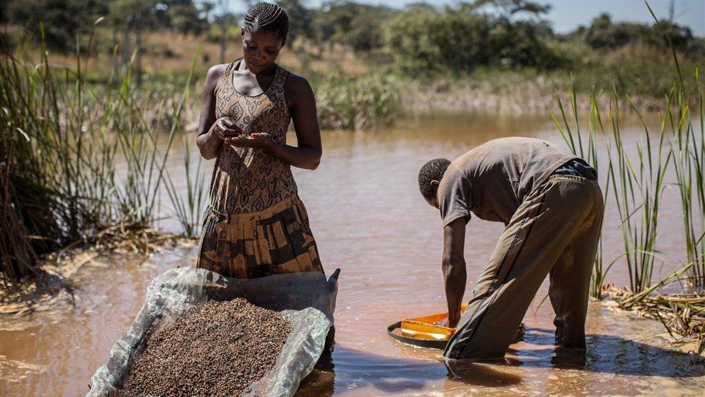 Een vrouw haalt kobalt uit de modder in de buurt van een mijn in Congo.