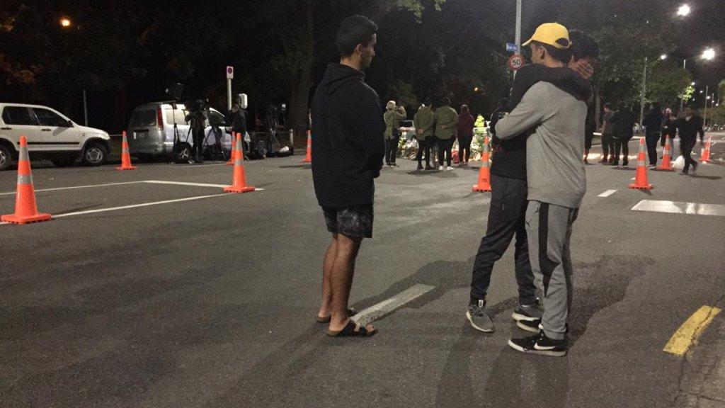 Mensen troosten elkaar op straat.