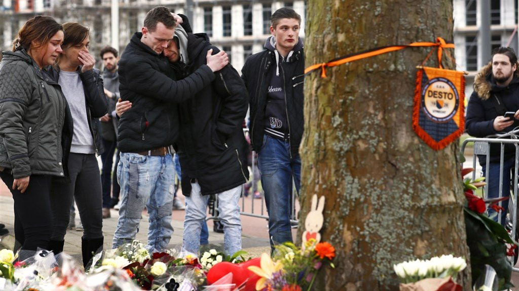 Belangstellenden omhelzen elkaar bij de bloemen op het 24 Oktoberplein in Utrecht.
