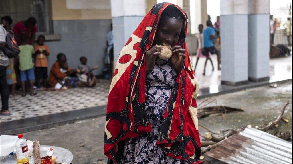 Een vrouw eet een stuk brood in een middelbare school in Beira waar nu getroffen mensen zoal zij worden opgevangen.