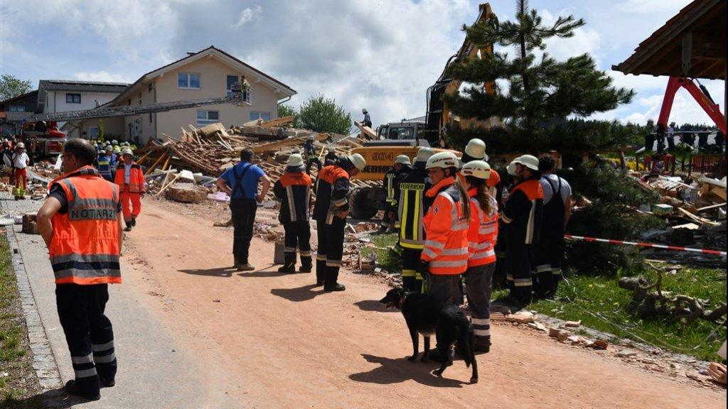 Reddingswerkers bij het verwoeste huis.