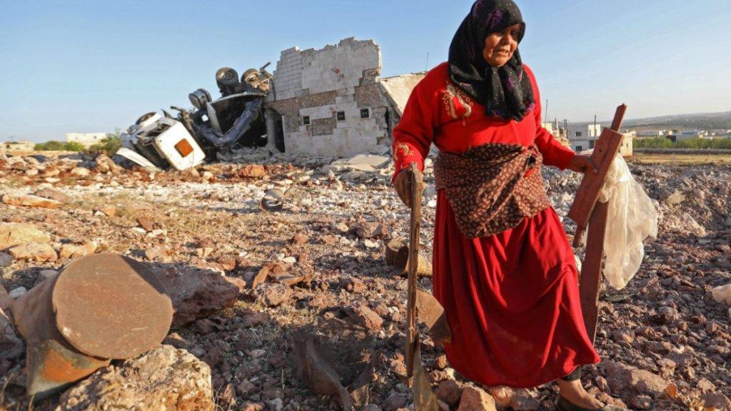 Een vrouw zoekt bezittingen tussen de puinhopen na een luchtaanval in Idlib.