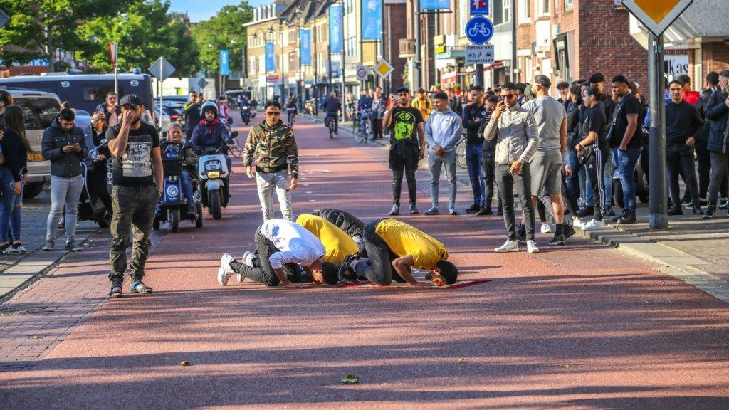 Enkele tegendemonstranten bidden demonstratief midden op de weg.