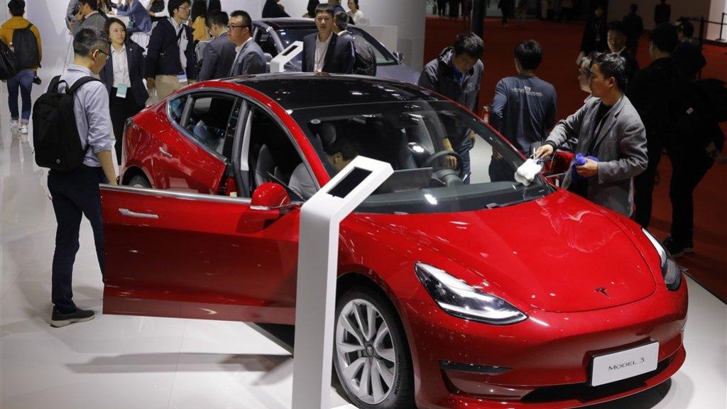 Bezoekers vergapen zich aan een Tesla Model 3 op de autoshow in Shanghai, eerder dit jaar.