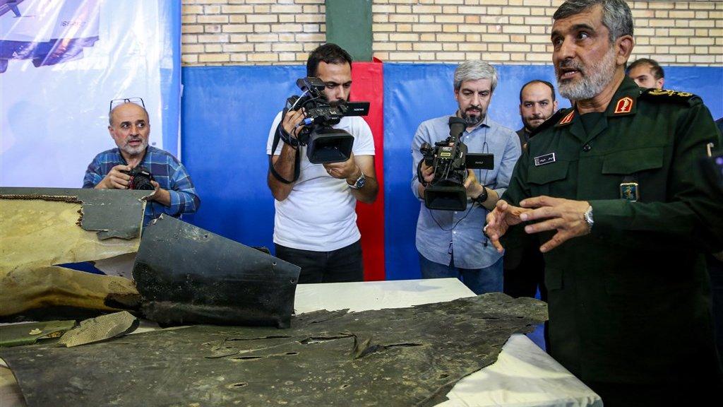 Ali Hajizadeh van de Iraanse Revolutionaire Garde bij wat wrakstukken van de neergehaalde drone zouden zijn.