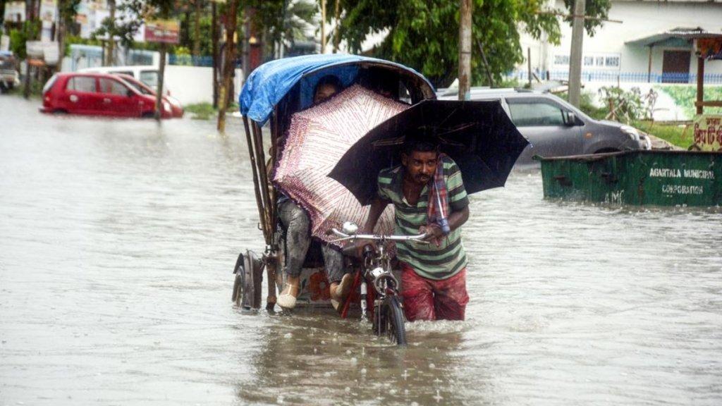 Een riksjarijder in India probeert ondanks het noodweer toch iemand op de plaats van bestemming te brengen.