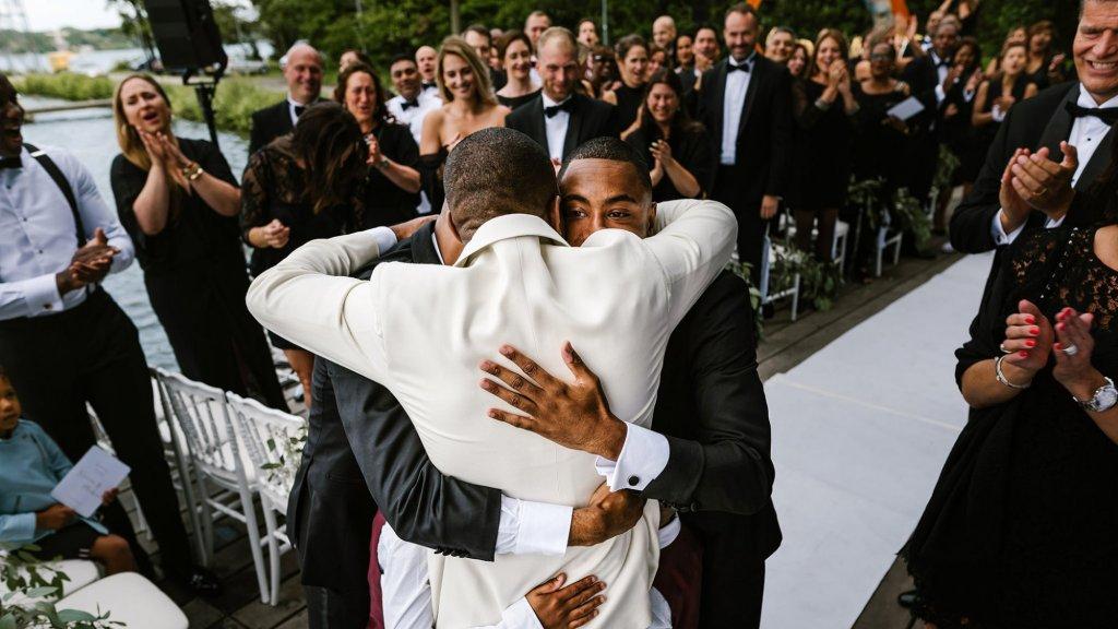 De bruidegom wordt omhelst door zijn getuigen.