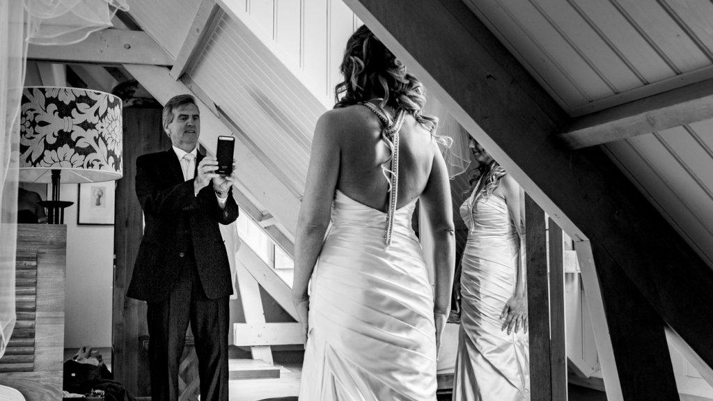 De vader van de bruid fotografeert zijn dochter.