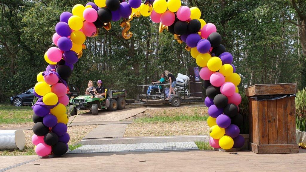 Bezoekers worden met aanhangwagen naar het festivalterrein gebracht.