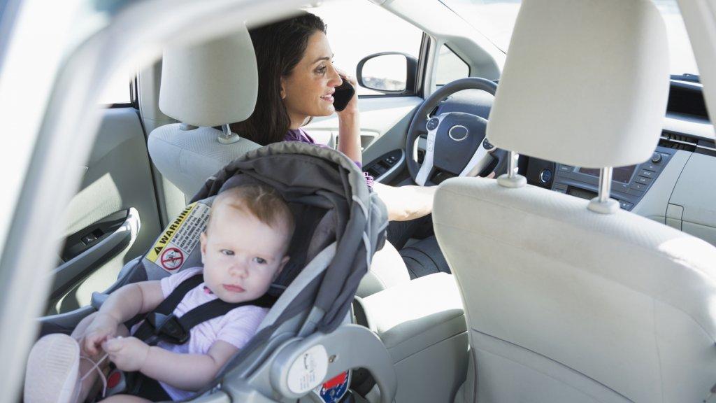 Een moeder met haar kind achterin de auto. (Archieffoto)