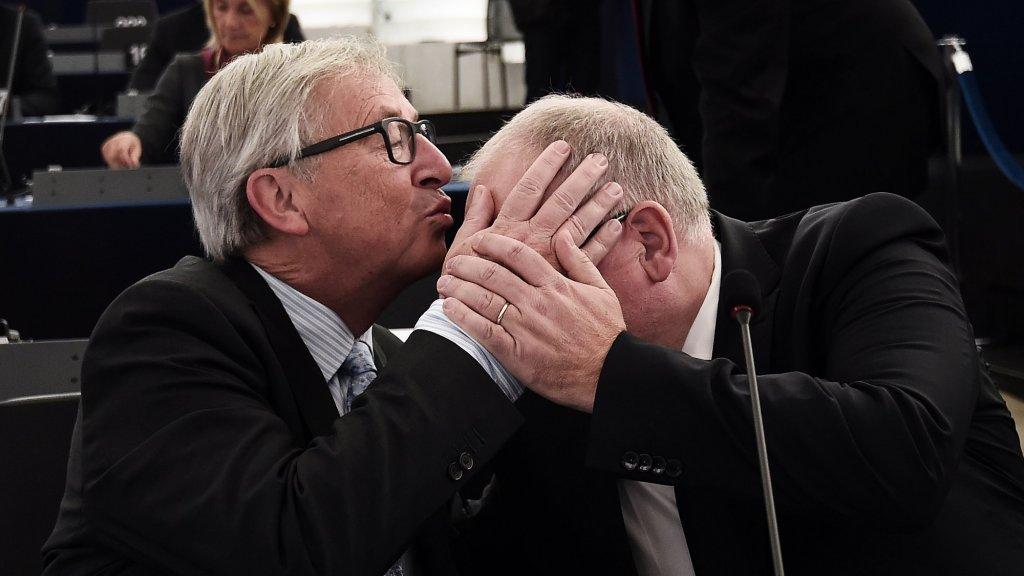 Het handelsmerk van Juncker: de kus. Hier is de Nederlandse Eurocommissaris Frans Timmermans het mikpunt van zijn lippen.