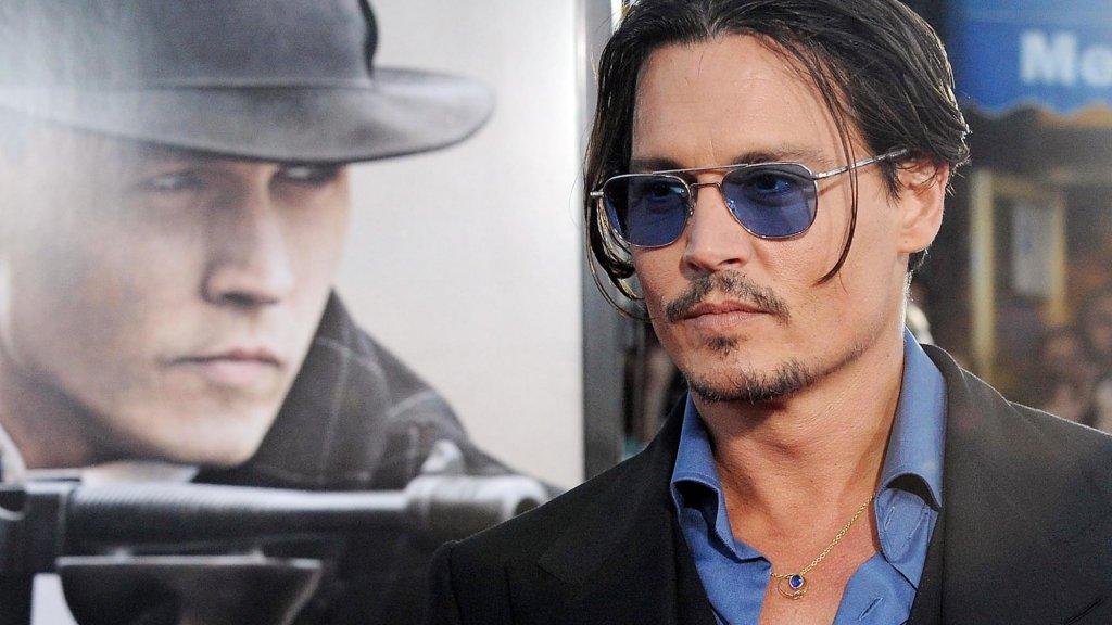Johnny Depp naast de poster van Public Enemies.