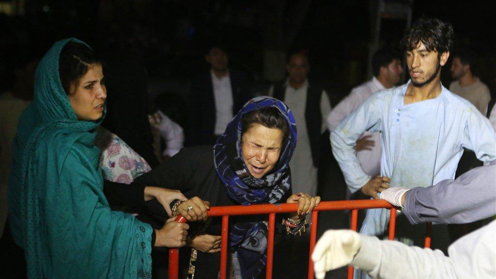 Een Afghaanse vrouw, buiten bij het ziekenhuis, is in tranen.