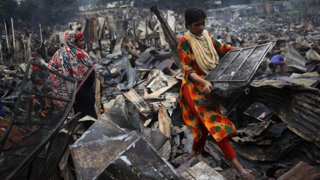 Vandaag, een dag na de brand in Dhaka, proberen inwoners spullen bij elkaar te rapen.