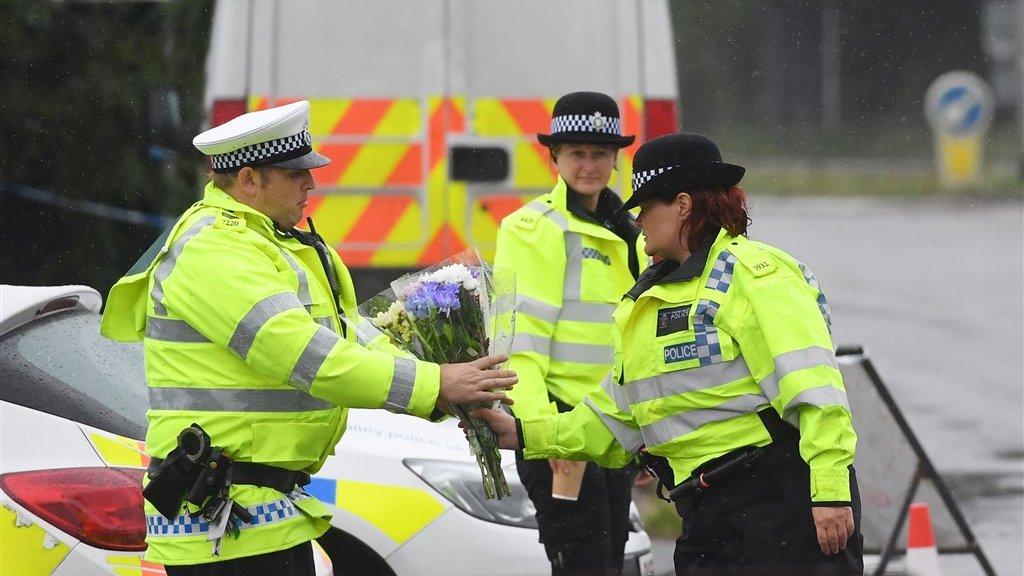 Collega-agenten leggen bloemen op de plek waar Andrew is omgekomen.