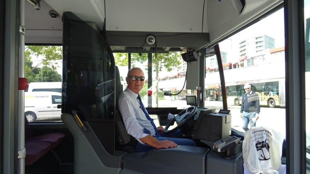 Wim Groeneweg achter het stuur van 'zijn' bus.