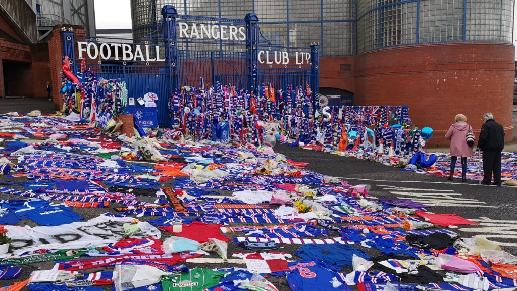 Bloemen, vlaggen en sjaals voor het stadion van Rangers.