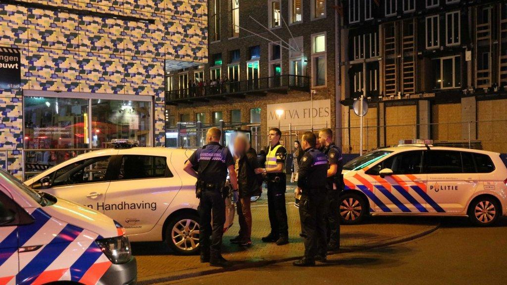 De verdachte wordt door de politie gearresteerd.