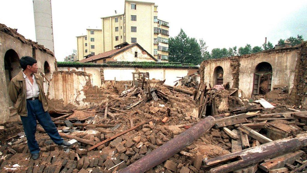 Een man staat naast zijn verwoeste huis in Peking, dat plaats moest maken voor de aanleg van een snelweg (1998).