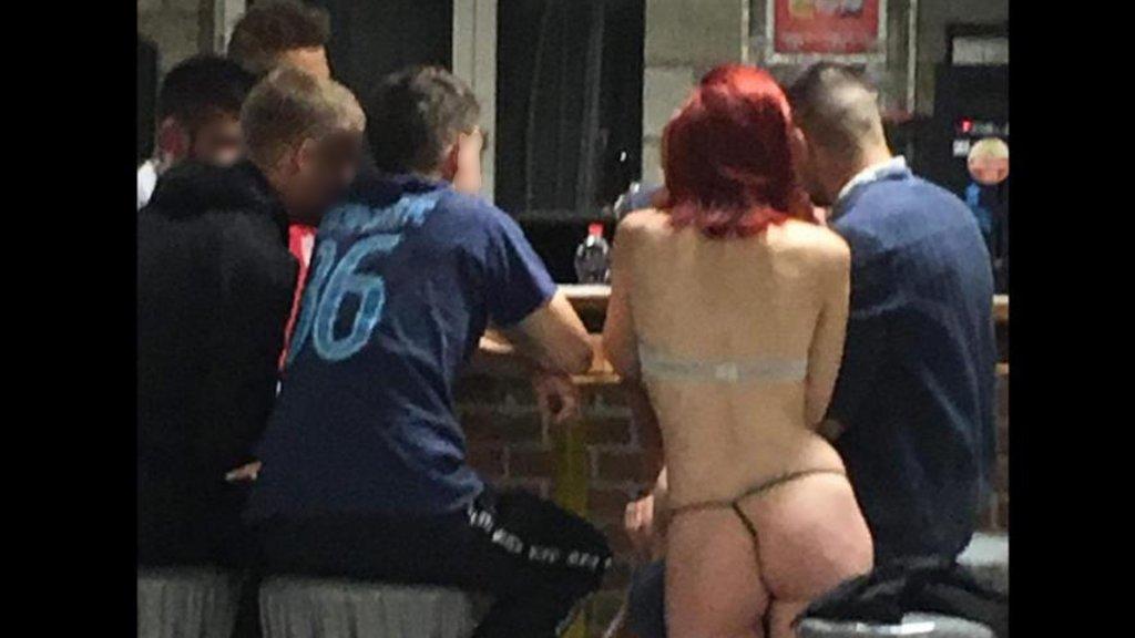 De vrouw zit halfnaakt aan de bar met een aantal spelers