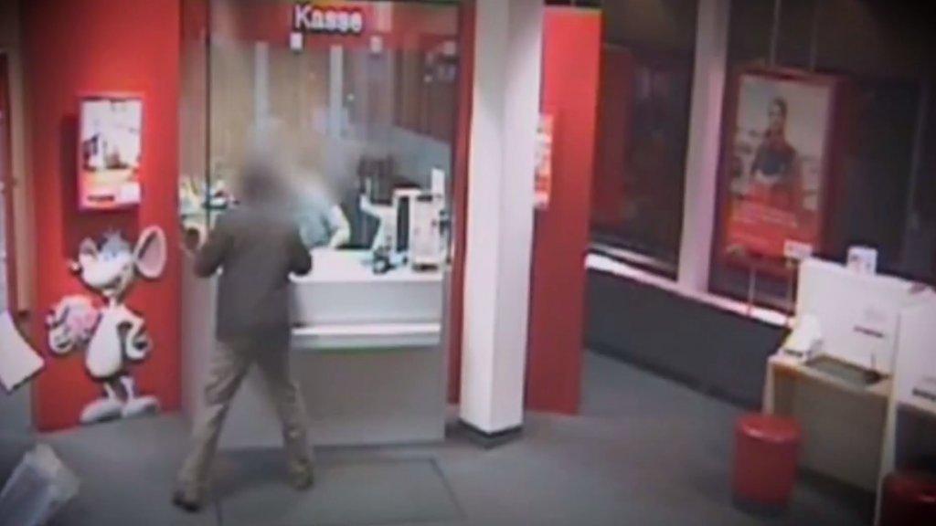 Op deze beelden, gemaakt door een beveiligingscamera, is Michael Jauernik te zien terwijl hij een overval pleegt.