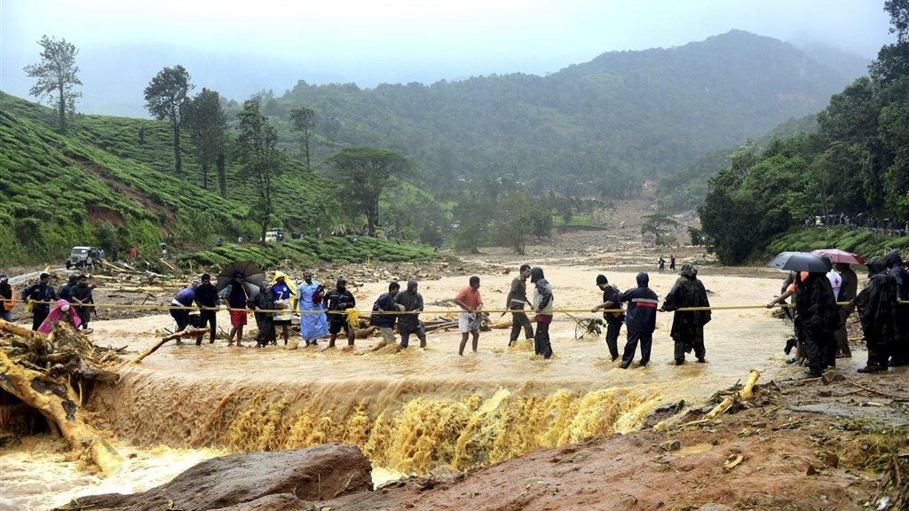 Inwoners van Kerala op weg naar hogergelegen gebied tijdens een overstroming.