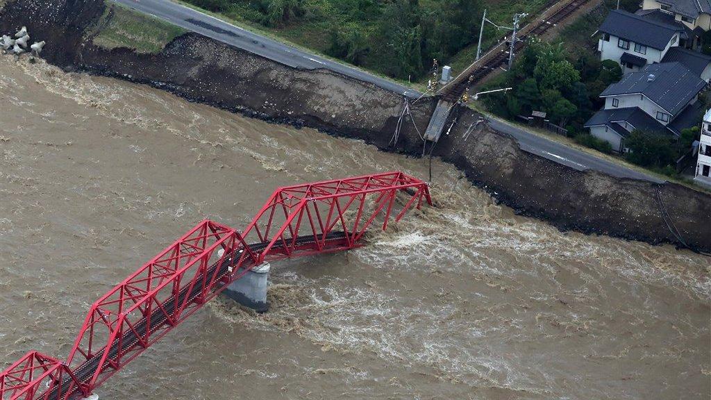 Een beschadigde treinbrug over de gezwollen Chikuma-rivier in Nagano.
