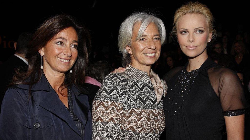 Modeliefhebber Lagarde bij de Paris Fashion Week met onder andere actrice Charlize Theron (r).