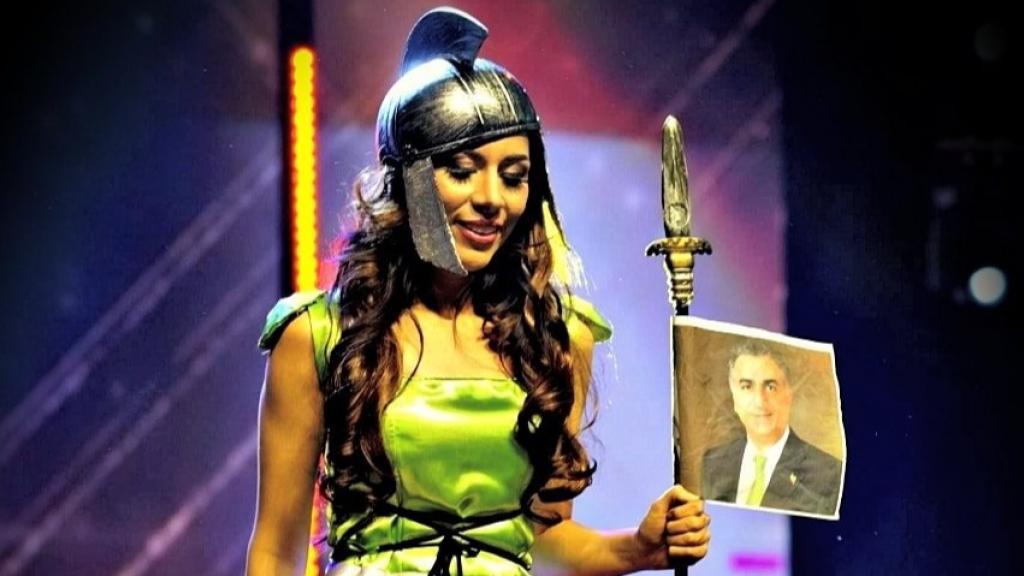 Bahari tijdens de missverkiezing met een foto van een criticus van het Iraanse regime.