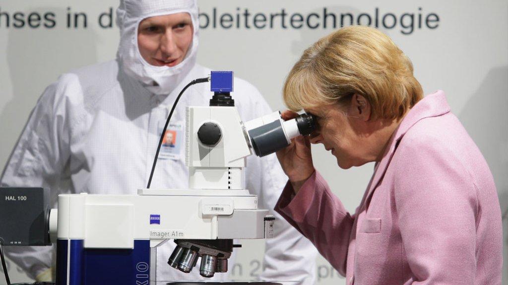 Bondskanselier Angela Merkel werpt een blik op een siliconenwafer in Dresden.