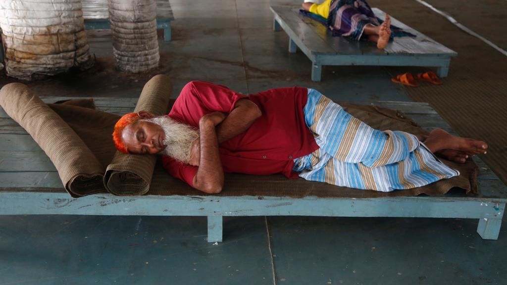 Medewerkers van de scheepswerf doen een dutje. Er is even niks te doen omdat het scheepsverkeer in twee grote havens uit voorzorg is stilgelegd.
