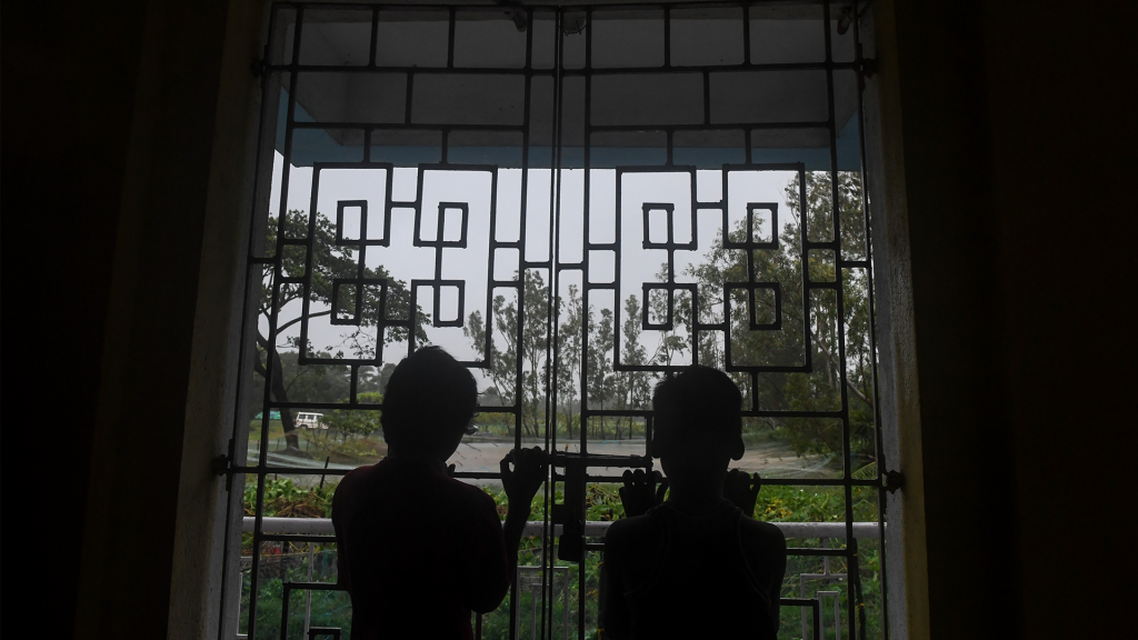 Twee kinderen kijken door het raam van hun opvangcentrum. Bangladesh heeft 5000 schuilplaatsen opgezet. In totaal moeten 1,5 miljoen mensen worden geëvacueerd. Het is een race tegen de klok: gisteren waren nog maar 100.000 mensen in veiligheid gebracht.