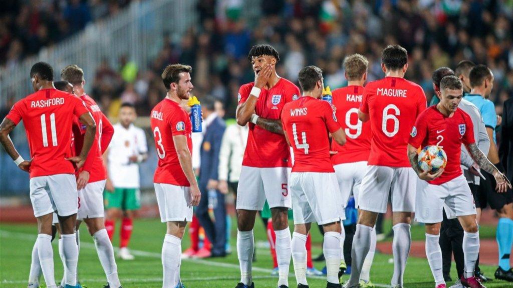 Spelers van Engeland wachten tot de wedstrijd wordt hervat