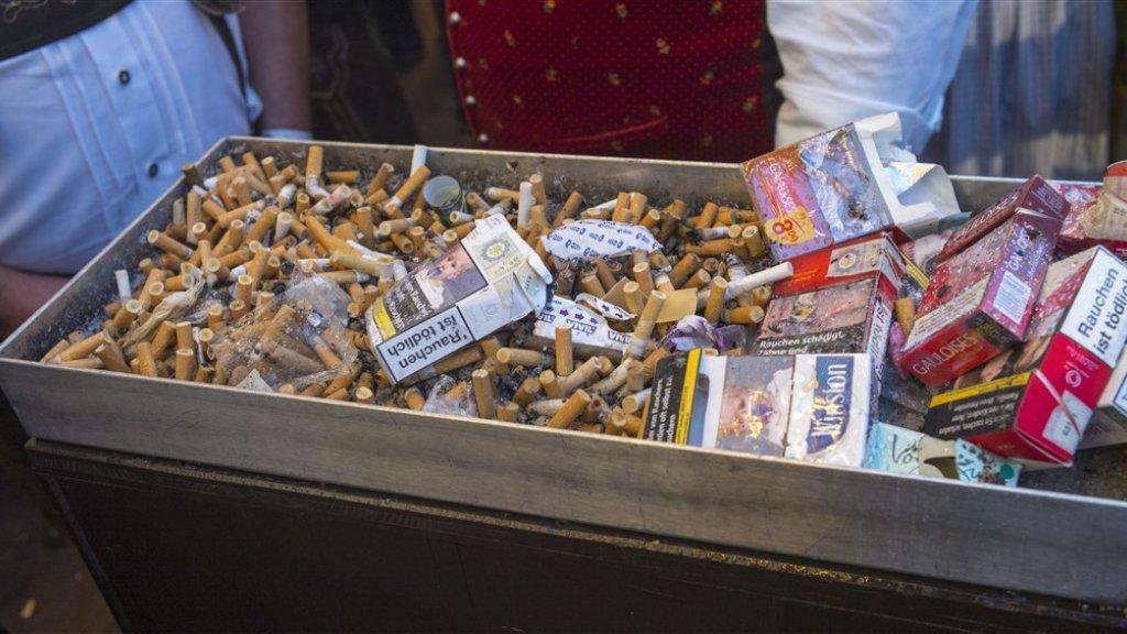 Sigarettenpeuken in een gigantische asbak op het terrein van het Oktoberfest in München