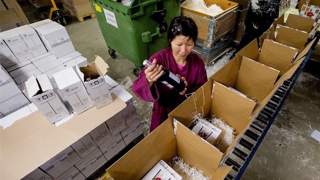 Een werknemer pakt een kerstpakket in.