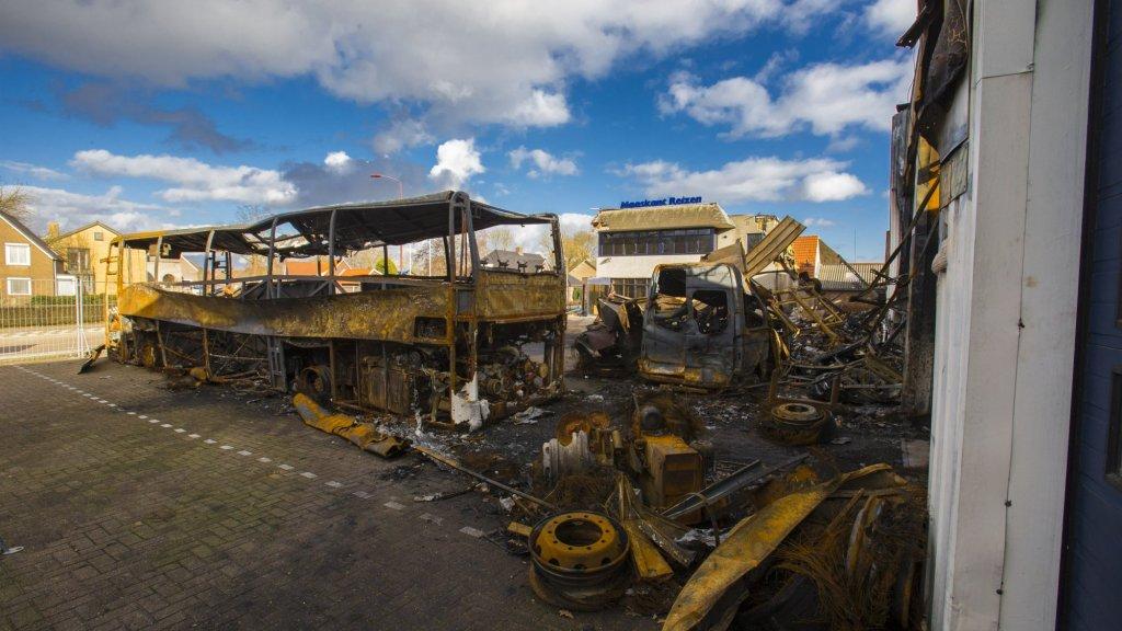 Na de brand blijven uitgebrande bussen over.