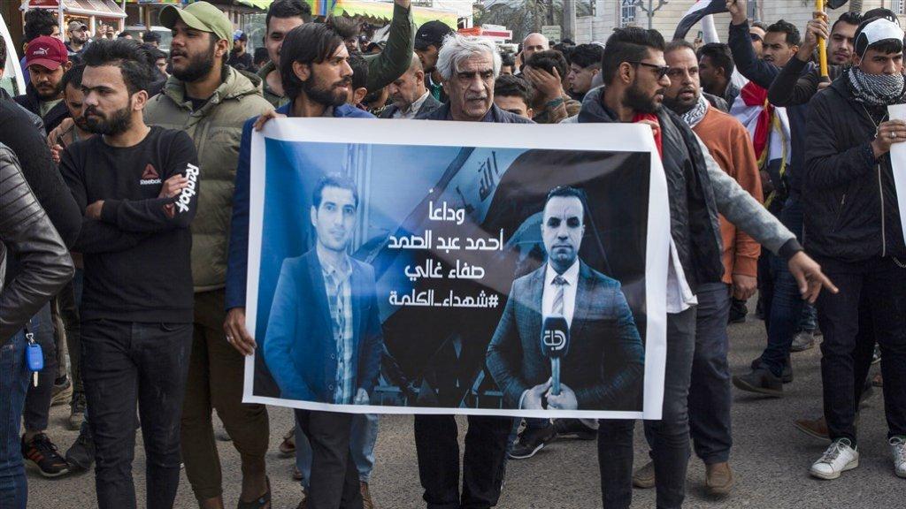 Demonstranten in Basra met een spandoek met foto's van de vermoorde Ahmed Abdelsamad en Safaa Ghali.
